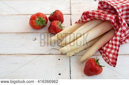 Fresh White Asparagus And Strawberries On White Vintage Table. Food Photography With Short Depth Of