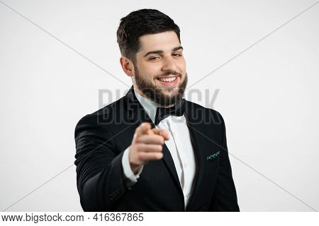 Charming Man In Tuxedo Points Index Finger Into Camera Lens And Winks, Flirts. Hey, You. Guy With Be