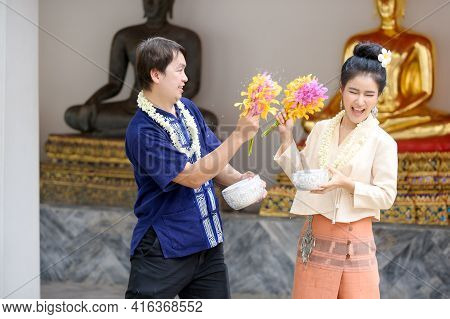 Young Thai Men And Women In Traditional Thai Dress Hold Flowers Splashing Water For Fun At The Songk