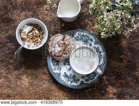 Cozy Homemade Breakfast - Greek Yogurt With Granola, Chocolate Meringue, Cappuccino On A Wooden Tabl