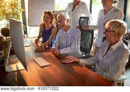 Group of business woman has a good time while working at the desk in a relaxed atmosphere in the office together. Business, office, job