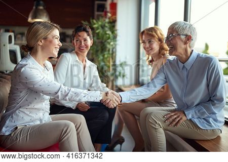 Group of senior female office staff getting know their new young female colleague while taking a break in a friendly atmosphere at workplace. Business, office, job