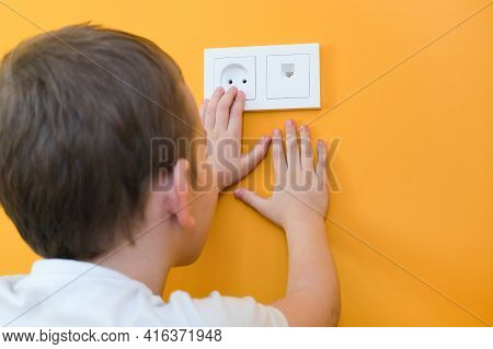 Dangerous Situation At Home. Child Playing With Electrical Socket. Hands Reach For The Electrical So