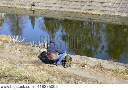 A Man On The Bank Of The River Fishing Rod. The Fisherman Enjoys Fishing.