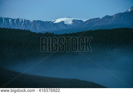 Atmospheric Mountains Landscape With Dense Fog And Great Snow Mountain Top Under Twilight Sky. Alpin