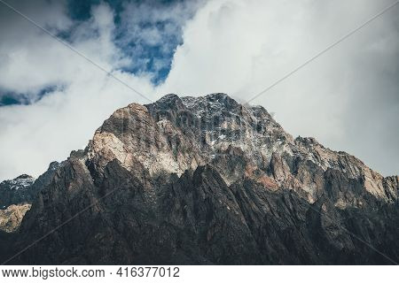 Mountain Landscape With Rocks With Snow In Sunlight And Low Clouds On Top. Awesome Rocky Wall With S