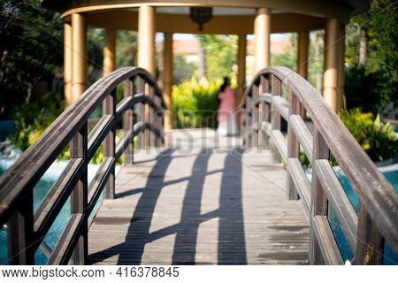 Locked Shot Of Arched Wooden Bridge With Swimming Pool On Both Sides With Blue Water And Out Of Focu