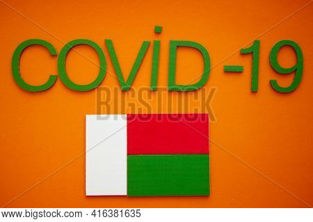 Flag Of Madagascar And Word Covid-19 Made Of Green Cardboard Letters, Isolated On Orange Background.