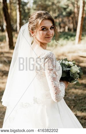 Lovely Bride With A Bouquet In Her Hands Outside. Bride With White Hair In The Forest. Portrait Of T