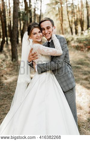 The Groom Hugs The Bride With A Smile On His Face. Lovely Wedding Day Of Cute Couple. Rustic Wedding