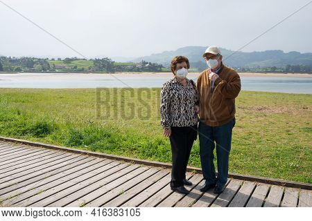 Aged Couple 70-80 Walking In Rodiles, Near The River And Puntal Forest In The Background, Asturias.