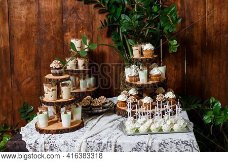Candy Bar On Wooden Wedding Party With A Lot Of Different Candies, Cupcakes, Souffle And Cakes. Deco