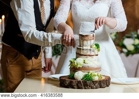 Groom In Suit And Bride In White Dress Cut Beautiful Multi Level Naked Wedding Cake, Decorated With