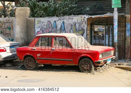 Giza, Egypt - January 26. 2021: Small Red Car Fiat 128 In The City Street.