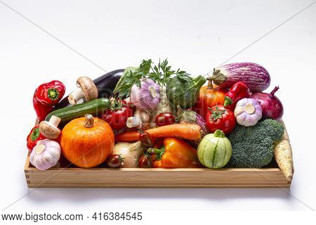 Assorted Organic Vegetables In A Wooden Box On A Light Background.