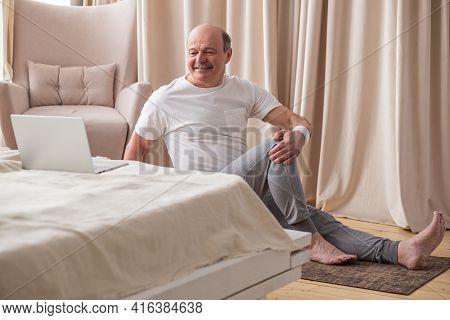 Senior Caucasian Man Doing Yoga Spine Twisting Pose