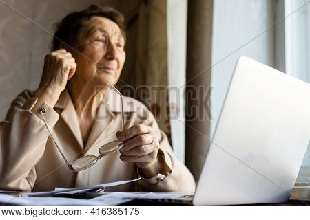 Pensioner Read Countless Papers And Is Very Focused. Senior Woman Calculating Taxes At Home. Retired