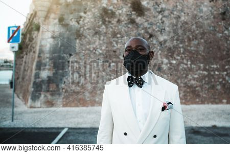 Portrait Of A Bald Bearded Dapper African Guy In A White Suit With A Dotted Bow Tie And A Virus Prot