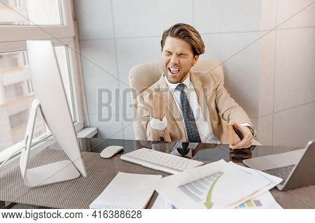 Overjoyed Male Employee In Stylish Formal Suit Is Sitting At The Desk, Feeling Euphoric, Got A Job P