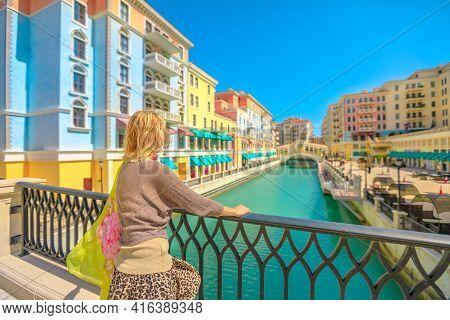Blonde Woman On Balcony Looking Canals Of Venice In Doha Qatar. Caucasian Tourist Enjoys Qanat Quart