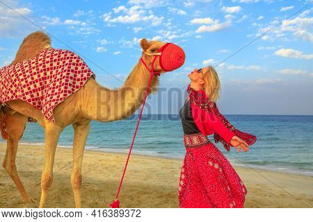 Travel In Persian Gulf. Carefree Blonde Woman With Camel On Beach Of Khor Al Udaid In Persian Gulf,