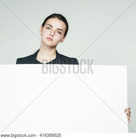 Young Pretty Brunette Girl With Placard Shit Copyspace On White Background Wearing Business Costume