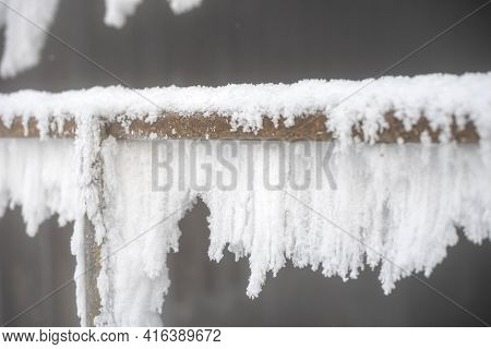 Icy Metal Railing. Ice And Icicle Formation.