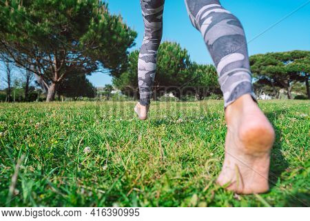 Barefoot Walking. Sporty Barefoot Woman Walking On The Green Grass. Young Female Legs Running Barefo