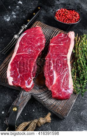 Raw Marbled Beef Meat Sirloin Steak. Black Background. Top View