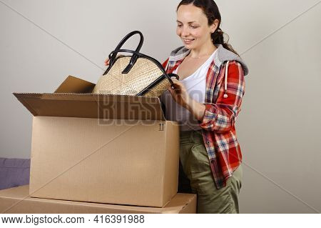Unpacking The Parcel Amazon. A Woman Takes Out Her Hat And Bag For Summer Vacation. Concept Of Succe