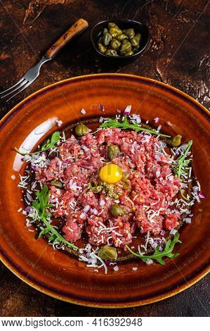 Beef Steak Tartare With Raw Egg Yolk, Pickled Capers And Parmesan Cheese. Dark Background. Top View