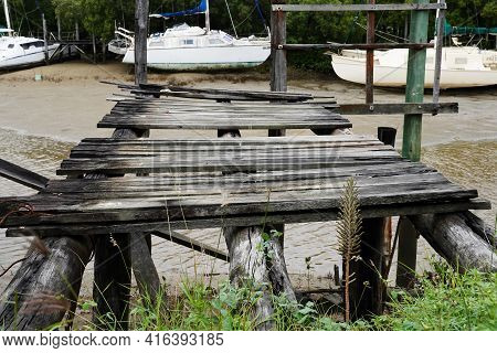 Yeppoon, Queensland, Australia - April 2021: An Old Falling Down Wooden Jetty With Boats Moored At L