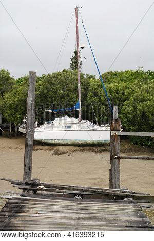 Yeppoon, Queensland, Australia - April 2021: Boat Moored In A Coastal Creek At Low Tide Amongst Mang
