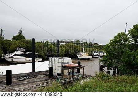 Yeppoon, Queensland, Australia - April 2021: Old Timber Jetty On Creek Bank With Boats Moored In The