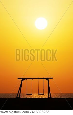 Silhouette Of Wooden Swing With Beautiful Sunset On The Hill Near The Sea