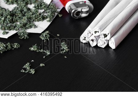 Marijuana Joints Or Hemp On Black Wood Background. Narcotic Recreational Drugs Concept
