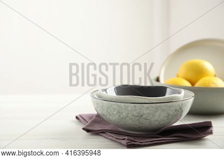 Set Of Clean Dishware And Lemons On White Wooden Table. Space For Text