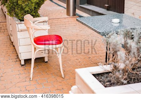 White And Red Classic Soft Chair Stands Near Granite Table With White Ashtray. Traditional. Sidewalk
