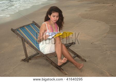Pretty Asian woman reading and relax on beach bed.