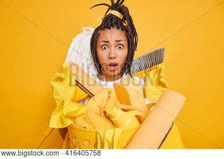 Puzzled Nervous Afro American Woman With Dreadlocks Stares Shocked At Camera Surrounded By Cleaning