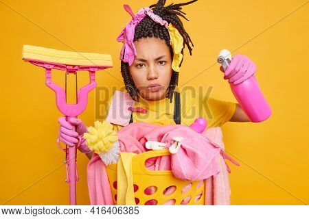Serious Scrupulous Afro American Housewife Has Dreadlocks Holds With Cleaning Accessories Stands Nea