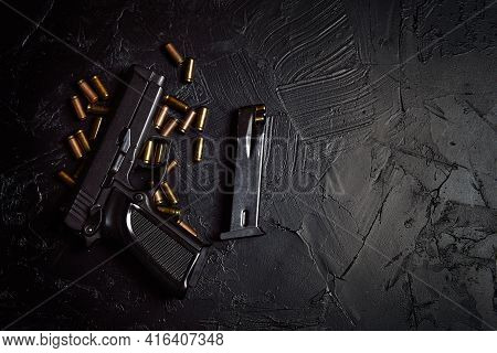 Firearms On Dark Background. Top View Of Gun And Cartridge With Bullets. Pistol For Defense Or Attac