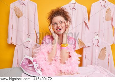 Domestic Work And Housekeeping Concept. Pleased Dreamy Woman With Curly Hait Wears Transpatent Goggl
