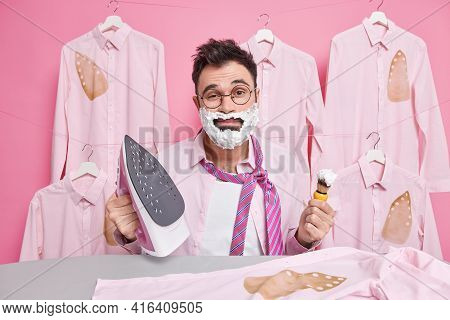 Tired Sleepy European Man Busy Shaving And Ironing Clothes In Morning Dresses And Prepares For Speci