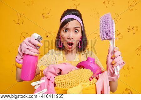 Indignant Brunette Female Housekeeper Busy With Daily Chores Looks Shocked At Camera Holds Spray Det