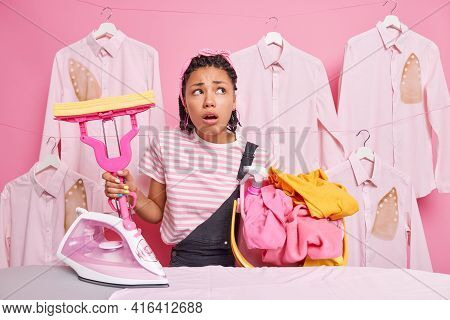 Dark Skinned Worried Housewife Busy Doing Housework Holds Basket Full Of Dirty Clothes Mop Poses Nea