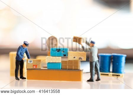 Miniature  People Postman Officer On Duty, He Prepares To Send A Box To Consumer