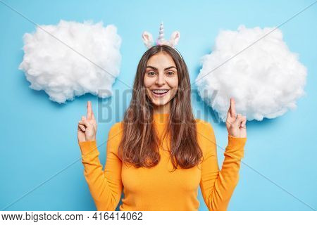 Happy Smiling European Woman Crosses Fingers Makes Wish Waits For Results Wears Unicorn Headband Ora
