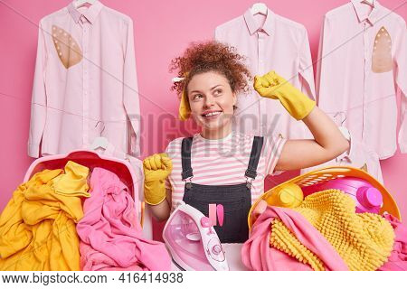 Domestic Chores And Laundering Concept. Positive Curly Haired Woman Dances With Arms Raised Poses Ne