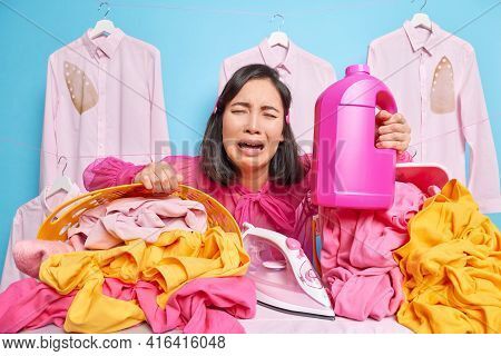Unhappy Disappointed Housewife Surrounded With Pile Of Laundry Holds Bottle Of Liquid Powder Feels F